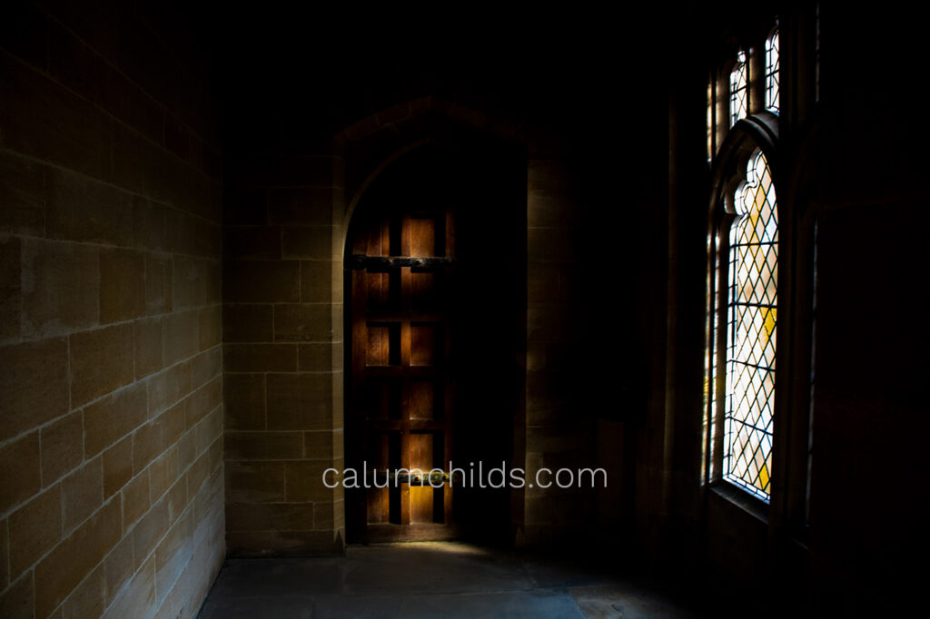 A dark brown door sits in the middle of a room, with a stained glass window on the right.