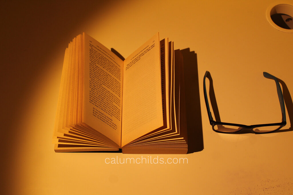 An open book containing small text and glasses.