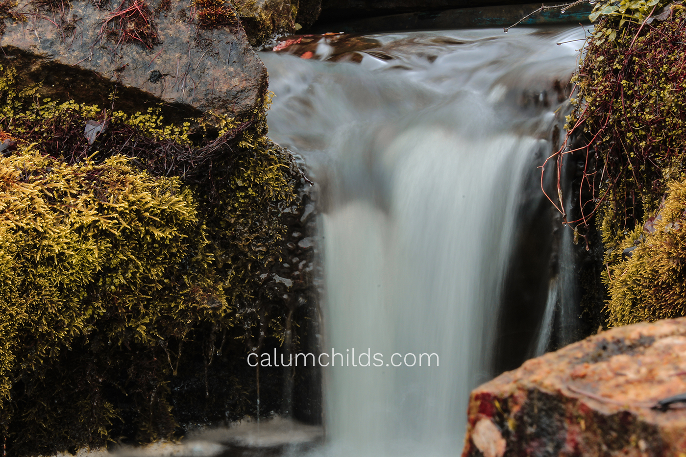A long-exposure shot of a waterfall surrounded by mainly yellow foliage.