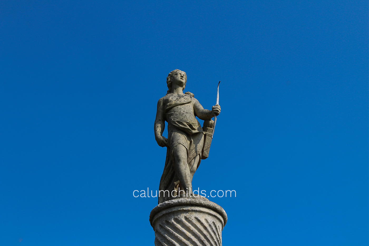A statue of a woman standing up holding a bow and arrow.