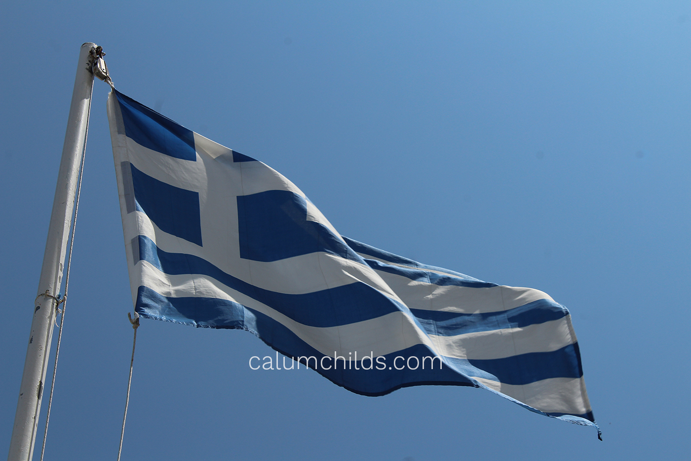 A large Greek flag waves on a grey pole with a blue sky behind it.
