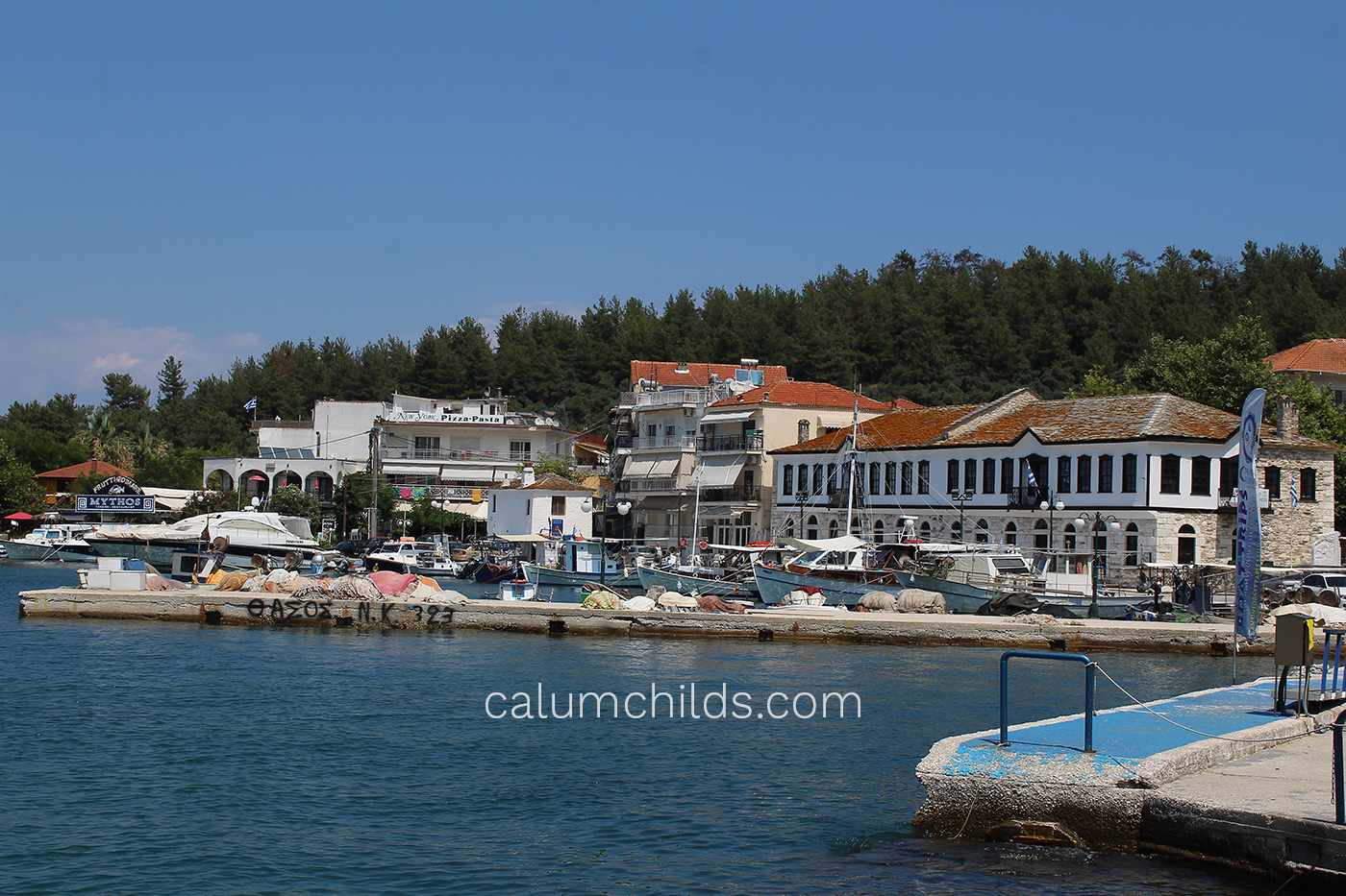 A series of traditional white Greek buildings with red roof tiles, and the dark blue sea in the background.