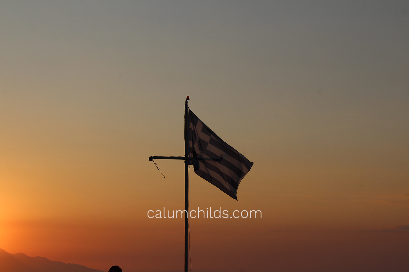 The Greek flag is waving on a white pole, with an blue-orange sunset sky behind it.